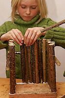 Kinder bauen Vogel-Nistkasten für Meisen, Vogelnistkasten, Nistkasten, Kinder kleben Holzstäbe aus Haselnussast als Seitenteil auf ein Brett