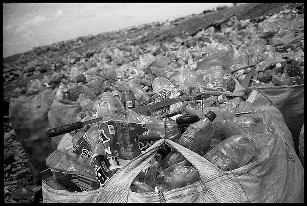 Oaxaca city dump. Bags of bottles await the recycling truck. A collector's machete lays on top. Each one of these bags, which takes hours of picking through garbage to fill, will net the collector about $3 US. The water shortage has made the plastic collection industry more viable over the last few years.....