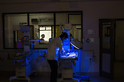 A nurse checks the baby as she sleeps under the phototherapy machine in the nursery of the Duncan Hospital in Raxaul, Bihar, India.