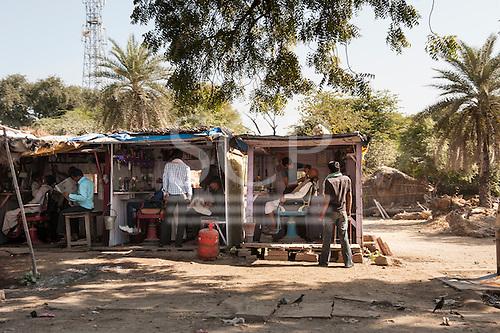 Rajasthan, India. Between Jaipur and Ranthambore. Barbers' kiosks at the roadside.