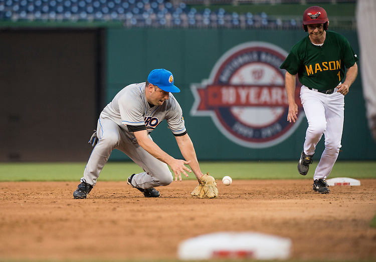 UNITED STATES - JUNE 11: Short stop Rep. Tim Ryan, D-Ohio, tries to get a handle on a ground ball as Rep. Rob Wittman, R-Va., runs to third base during the 54th Annual Roll Call Congressional Baseball Game at Nationals Park in Washington on Thursday, June 11, 2015. The Democrats beat the Republicans 5-2. (Photo By Bill Clark/CQ Roll Call)
