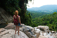 Girl standing on a cliff of Namuang waterfall, observing the nature of Samui island, Thailand