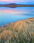 Alvord Desert, OR: Sunset sky reflects on the calm waters of Lower Borax Lake with Buckskin Mountain in the distance in the Pueblo Valley of Harner County