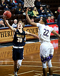SIOUX FALLS, SD - MARCH 10:  Christian Stewart #30 from Marian lays the ball up past Aziz Leeks #22 from the College of Idaho during their quarterfinal game at the 2018 NAIA DII Men's Basketball Championship at the Sanford Pentagon in Sioux Falls. (Photo by Dave Eggen/Inertia)