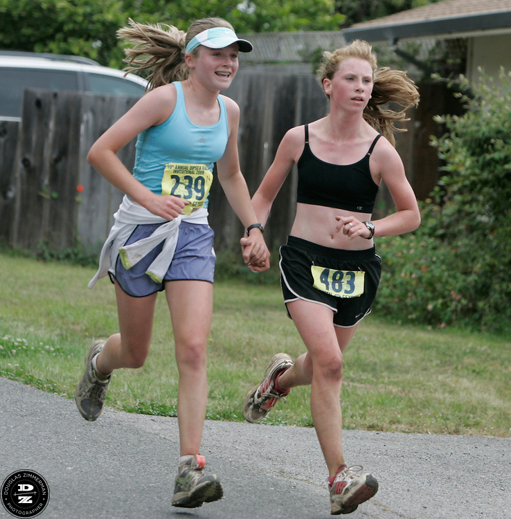Meghan Christie (239) of San Anselmo races hand-in-hand with (483) Summer Lawson of Forest Knolls at they race towards the finish line at the 99th running of the Dipsea Race at Sintson Beach State Park in Stinson Beach, Calif. on Sunday June 14th, 2009.
