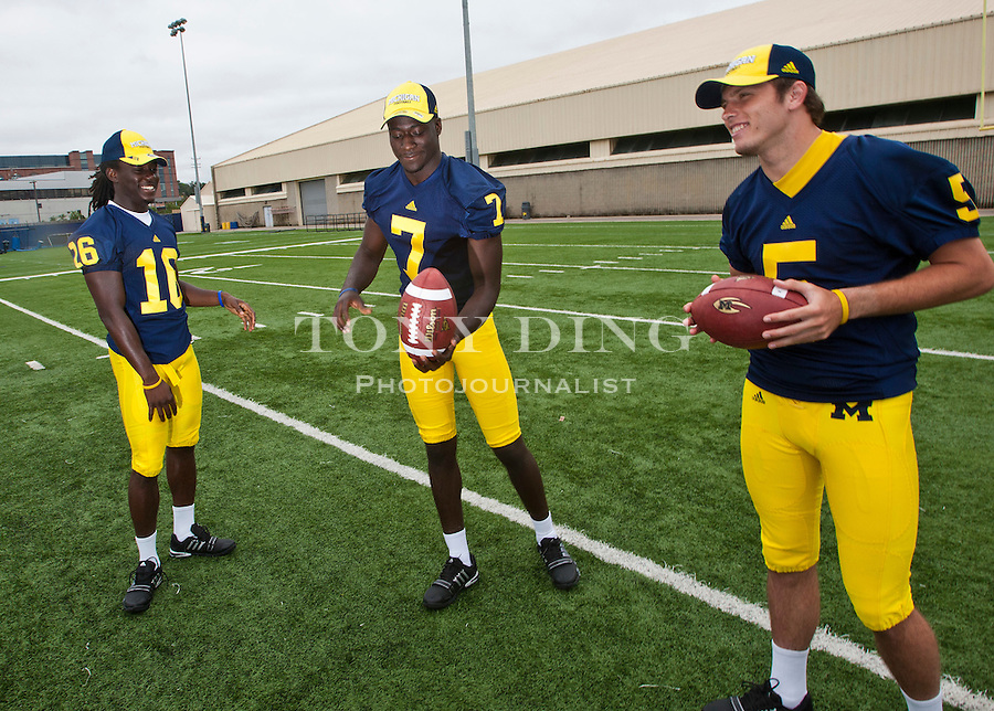Michigan quarterbacks Denard Robinson (16), Devin Gardner (7), and Tate Forcier (5) juggle footballs, at the annual NCAA college football media day, Sunday, Aug. 22, 2010, in Ann Arbor, Mich. (AP Photo/Tony Ding)