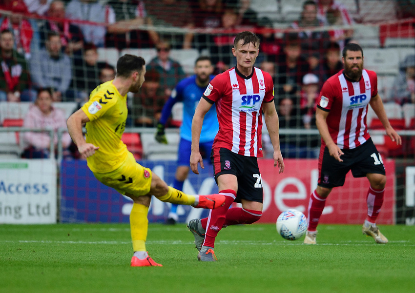 Lincoln City's Callum Connolly crosses down Fleetwood Town's Harrison Biggins<br /> <br /> Photographer Andrew Vaughan/CameraSport<br /> <br /> The EFL Sky Bet League One - Lincoln City v Fleetwood Town - Saturday 31st August 2019 - Sincil Bank - Lincoln<br /> <br /> World Copyright © 2019 CameraSport. All rights reserved. 43 Linden Ave. Countesthorpe. Leicester. England. LE8 5PG - Tel: +44 (0) 116 277 4147 - admin@camerasport.com - www.camerasport.com
