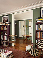 A pair of purple, lacquered bookcases designed by Nicolo as a series of cubes flanks the wide, floor-to-ceiling doorway between the drawing room and the dining room