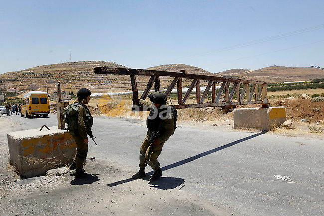 Israeli soldiers close a barrier blocking the road at the West Bank Al-Fawwar refugee camp, south of Hebron on July 3, 2016, as the army keeps the town under lockdown following clashes and attacks that killed two Israelis. Israeli troops locked down Hebron and surrounding villages after two Israelis were killed in Palestinian attacks nearby.The crackdown comes amid a flare-up in nine months of deadly violence as the end of the Muslim fasting month of Ramadan looms, and after key diplomatic players called for urgent steps by both sides to revive the moribund peace process. Photo by Wisam Hashlamoun