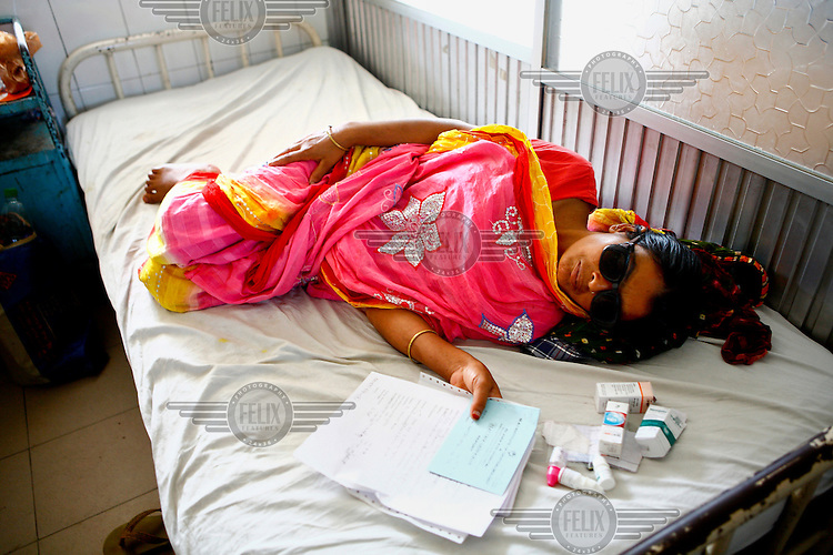 A woman, wearing dark glasses following a procedure, lie on a bed surrounded by medications at the Islamia Eye Hospital. Founded in 1960, about 20,000 eye surgeries are performed in the main hospital annually, that is approximately 10% of the total cataract surgeries in the country.
