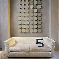 An artwork of circular shapes hangs on the wall behind a simple, white upholstered sofa.