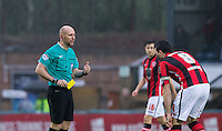 Referee Andy Davies hands Peter Murphy of Morecambe an early yellow card during the Sky Bet League 2 match between Wycombe Wanderers and Morecambe at Adams Park, High Wycombe, England on 2 January 2016. Photo by Andy Rowland / PRiME Media Images