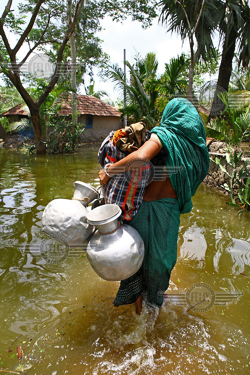 A woman carries all that she can through the floodwaters. Thousands of people were displaced in Shyamnagar Upazila, Satkhira district after Cyclone Aila struck Bangladesh on 25/05/2009, triggering tidal surges and floods..