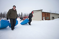 Saturday February 19, 2011.  Volunteer Iditarod Air Force pilots Greg Fischer (L) and John Norris drag bales of straw toward their Cessna airplanes at the Willow, Alaska airport as they begin to take a load of musher's dog food, straw and people food to the Yentna checkpoint.