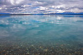 Cumulus clouds reflected in the calm waters of Lake Pukaki, Mackenzie District, Canterbury, South Island, New Zealand.