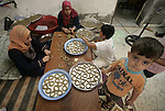 A Palestinian family prepare a biscuits on the occasion of Eid al-Fitr in Rafah, southern Gaza Strip on September 12, 2009. According to the Central Bureau of Statistics, the increase in average prices is still accelerating, doubling the need to buy clothes, food, footwear beginning of the school year in conjunction with the month of Ramadan and Eid al-Fitr. Photo By Abed Rahim Khatib