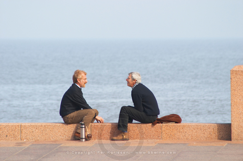 Two men sitting on a red stone bench. Men facing each other talking conversing and drinking mate herbal tea from a thermos hot water flask. Sea river in the background. In profile., on the riverside seaside walk along the river Rio de la Plata Ramblas Sur, Gran Bretagna and Republica Argentina Montevideo, Uruguay, South America