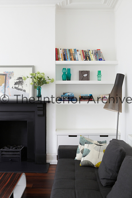 A corner of a white sitting room with a black fireplace and grey upholstered sofa. Books and coloured glassware are displayed on shelves built into the recess next to the chimney breast.