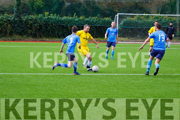 Tralee Classic's Martin Sweeney attemps to clear his defence as Dingle Bays Joe Kennedy and Joe Sheehy bear down on his attempt during their Munster Junior clash in Mounthawk Park on Sunday last.