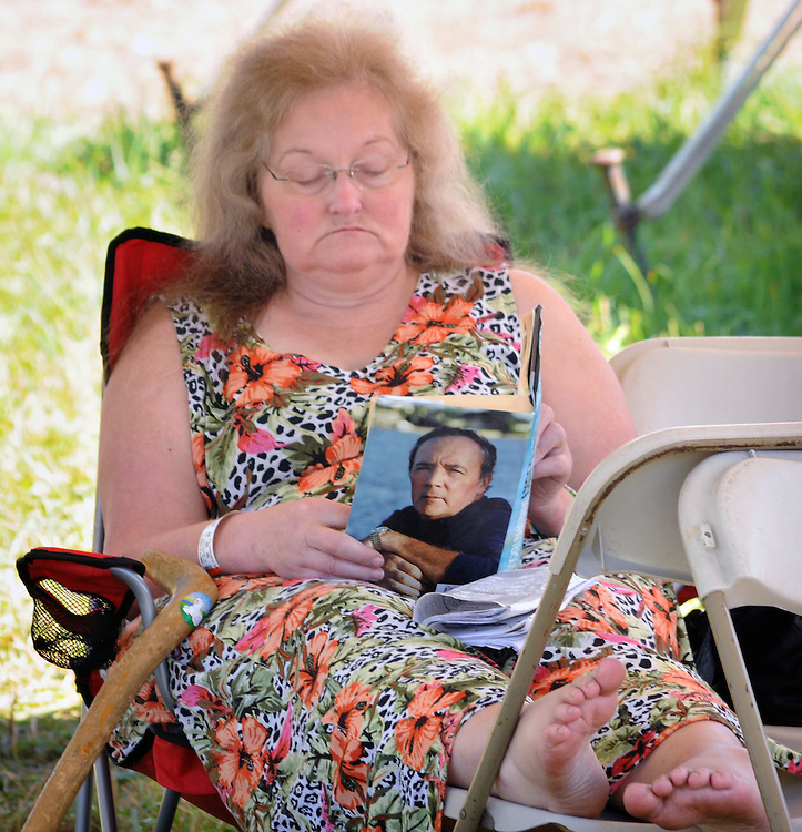 "A volunteer reads while waiting for the start of the 'Gospel Wake Up Call"" performance at the  Main Stage of the Falcon Ridge Folk Festival, held on Dodd's Farm in Hillsdale, NY on Sunday, August 2, 2015. Photo by Jim Peppler. Copyright Jim Peppler 2015."