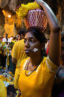 woman  with  spear thrilled through her cheeks while Thaipusam ceremonies inside Batu Caves, Kuala Lumpur, Malaysia, 2012. Thaipusam ceremonies, celebrated by tamile Hindu community in Malaysia, take place  in Sanctuary of Batu Caves at the border of Kuala Lumpur, each year around end of January or beginning of February, according to Hindu moon calendar. The event is paying hommage to Lord Murugan, a spirit or god created by Shiva to lead the army of gods against the army of evil demons, finally defeating the evil spirits. There are many ways to present offerings or sacrifices for this major religious event. Devotees mortify their bodies by carrying heavy kavaris with spears fixed in their skin or fruits, flowers and little post with holy milk fixed with hooks in their skin, ascending the stairways to the sanctuary in trance, `followed by assistant  taking care and musicians playing loud and fast rhythmic trance music.  Many families shave their head in a ritual before ascending the stairways, as part of rituals to obtain salvation for their ancestors.