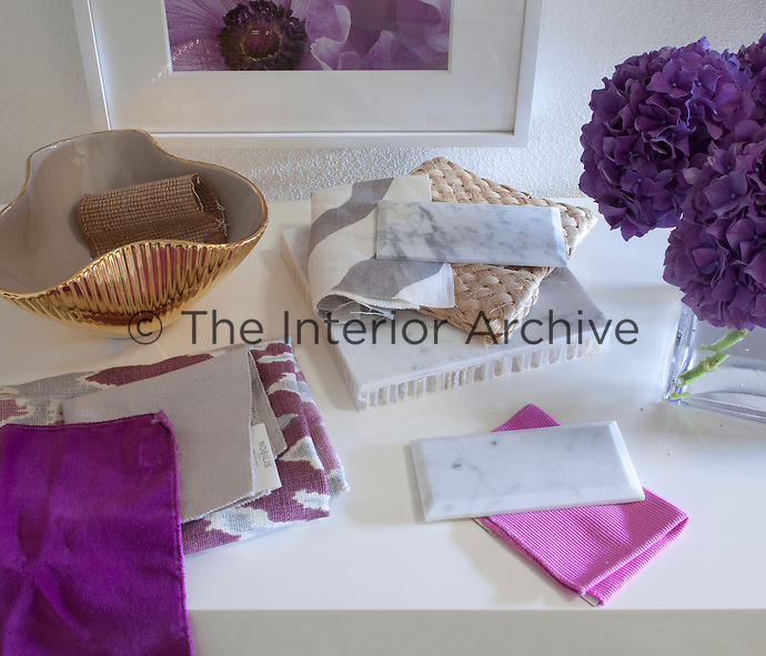 Samples of patterned and plain fabric in lilac and pink are arranged on a table. A gold bowl and purple hydrangea flowers are nearby.