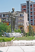 Street scene with a statue depicting a heroic Albanian military, apartment block buildings in the background. Monument to the national hero Isa Boletini. Shkodra. Albania, Balkan, Europe.