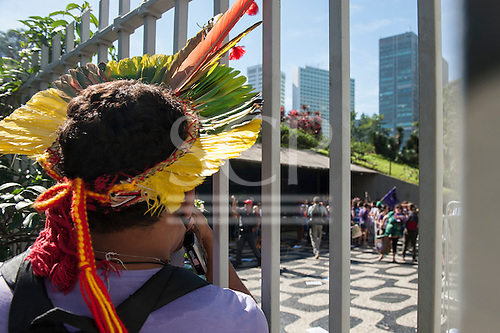 A Brazilian indigenous man watches through the bars as others who have climbed the fence demand to be heard at BNDES, the Brazilian National Development Bank. They had marched from the People's Summit at the United Nations Conference on Sustainable Development (Rio+20), Rio de Janeiro, Brazil, 18th June 2012. Photo © Sue Cunningham.