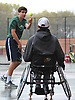 Bobby Bellino of Harborfields, left, tosses a ball to doubles partner Nate Melnyk after a volley in their varsity boys tennis match against host Smithtown High School East on Tuesday, Apr. 29, 2016. Melnyk, a wheelchair-using junior, played in his first varsity match, which was suspended in the first set due to the inclement weather. The match is set to resume on Monday, May 2.