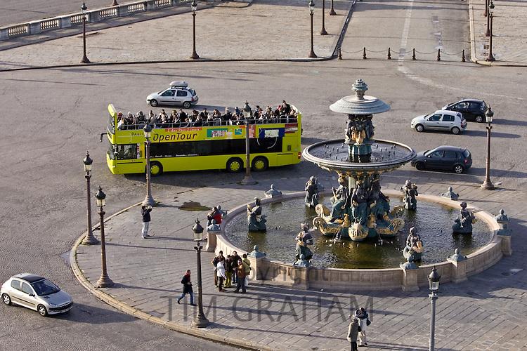 Open-air tour bus with tourists passes fountain in Place de la Concorde, Central Paris, France