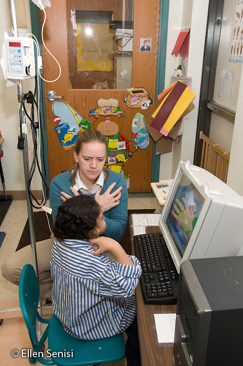 "MR / Albany, NY.Langan School at Center for Disability Services .Ungraded private school which serves individuals with multiple disabilities.Child uses a computer with letter recognition software while food is given through a gastric tube feeding. The teacher supervises and uses sign language (the word ""bear"") with him. Boy: 7, African-American, Pierre Robin syndrome, limited verbal output with expressive and receptive language delays, uses sign language partially to communicate.MR: Ris4; Smi24.© Ellen B. Senisi"