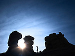 man hiking profile and sunshine surrounned by silhouetted sandstone rock formation pinnacles.  mesa de cuba, northern new mexico, usa.
