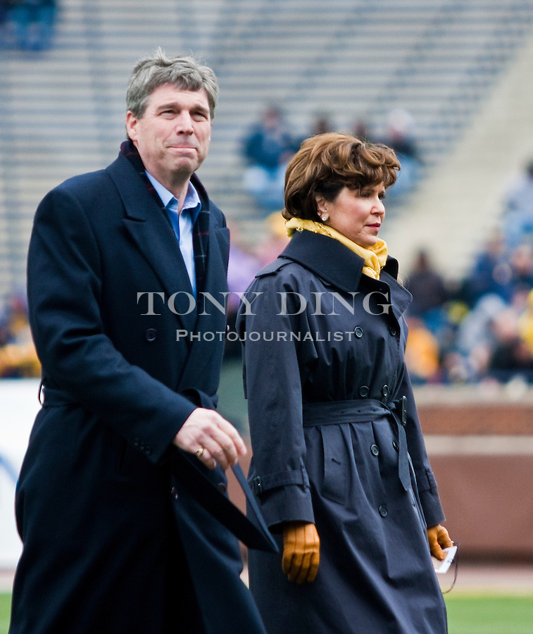 Michigan athletic director David Brandon, left, and his wife Jan, walk across the Michigan Stadium field to take their seats, before the Wolverines' spring football game, Saturday, April 17, 2010, in Ann Arbor, Mich. (AP Photo/Tony Ding)