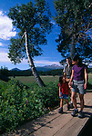 A young family enjoys a hike on along a wooden bridge during the summer, Rocky Mountains, Colorado