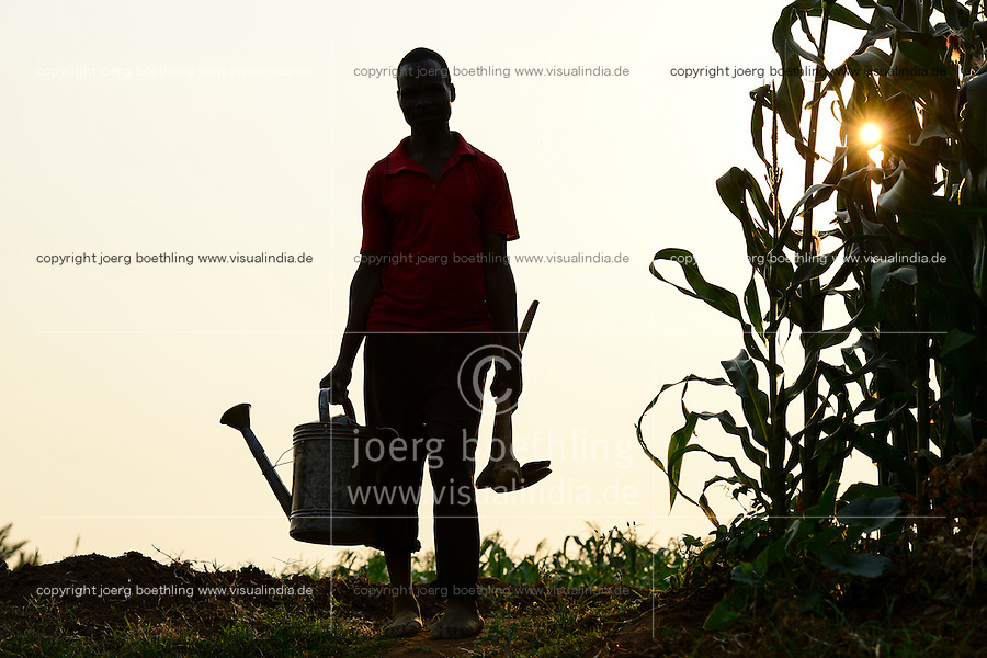Malawi, Thyolo, NGO CARD Churches Action in Relief and Development, irrigation in village Samuti, Farmer with can and hoe beside maize field