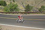 Man biking uphill on Lookout Mountain, west of Denver, Colorado, USA. .  John offers private photo tours in Denver, Boulder and throughout Colorado. Year-round.