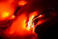 Red hot molten lava flows down a cliff into the sea between Kalapana and Hawai'i Volcanoes National Park, Big Island.