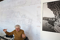 "Switzerland. Canton Ticino. Mendrisio. The architect Mario Botta in his office. On the wall, rolls of blueprints with architectural plans and technical drawings of the ""Thermalbad"" in Baden, Switzerland. A black and white picture from the San Carlino, built by Mario Botta in 1999  to celebrate the 400th anniversary of the birth of the architect Francesco Borromini. Standing almost 33 meters high and made up of 35,000 planks each 4,5 cm thick, mounted modularly with a ""separation"" of 1 cm, the large wooden model of San Carlino was held together with steel cables, in turn fixed to a steel frame weighing 90 tonnes. This life-size cross-section view of the church sat on a 22 square-meters platform just a few meters from the shore, at the end of the lake promenade and at the entrance to the Parco Ciani. The wooden model of San Carlino thus emerged from the deepest inlet of the lake gulf to act as a signpost to the exhibition about the young Borromini. 30.10.2017 © 2017 Didier Ruef"
