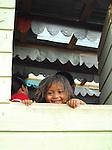 Village near Tegucigalpa. Honduran girl peering from window.