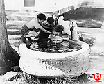 Young boys grab a drunk from the town fountain in Salisbury, June 1936.