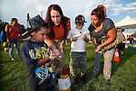 Amber Svensson, with CCSO Search and Rescue, helps D'Angelo Fillmore, 4, Tegan VanSickle, 7, and Maria Ramirez navigate the compass course at the 11th annual National Night Out hosted by the Carson City Sheriff's Office in Carson City, Nev., on Tuesday, Aug. 6, 2013. <br />