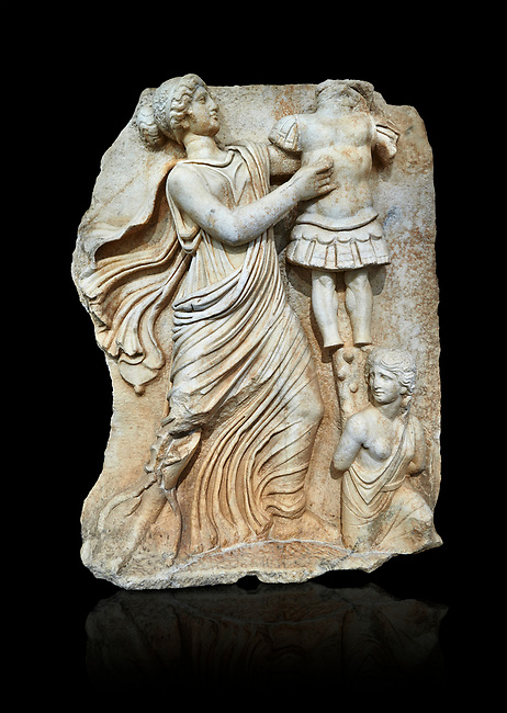 Roman Sebasteion relief  sculpture of a Goddess inscribing a trophy, Aphrodisias Museum, Aphrodisias, Turkey.   Against a black background.<br /> <br /> A draped goddess strides forward to inscribe a military trophy to which is bound a kneeling female captive. The goddess is probably a personification such as Honour, Virtue or Courage.