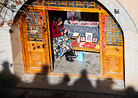 A paper artist makes intricate designs using a small knife as tourists look on from above the courtyard. This was the most popular shop for participants of our group visiting the pit yards near Sanmenxia.