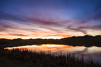 Sunset lights up the sky over a pond in the Bear Paw Mountains in central Montana.