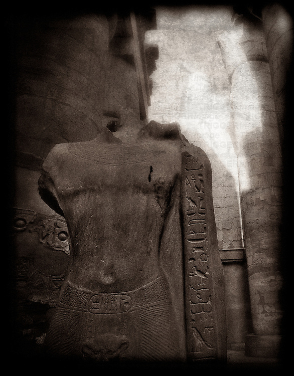 A black and white creative photograph of a ruined statue of an unknown person in The Great Hypostyle Hall, Karnak Temple, Egypt.   Built circa 1500 BC.