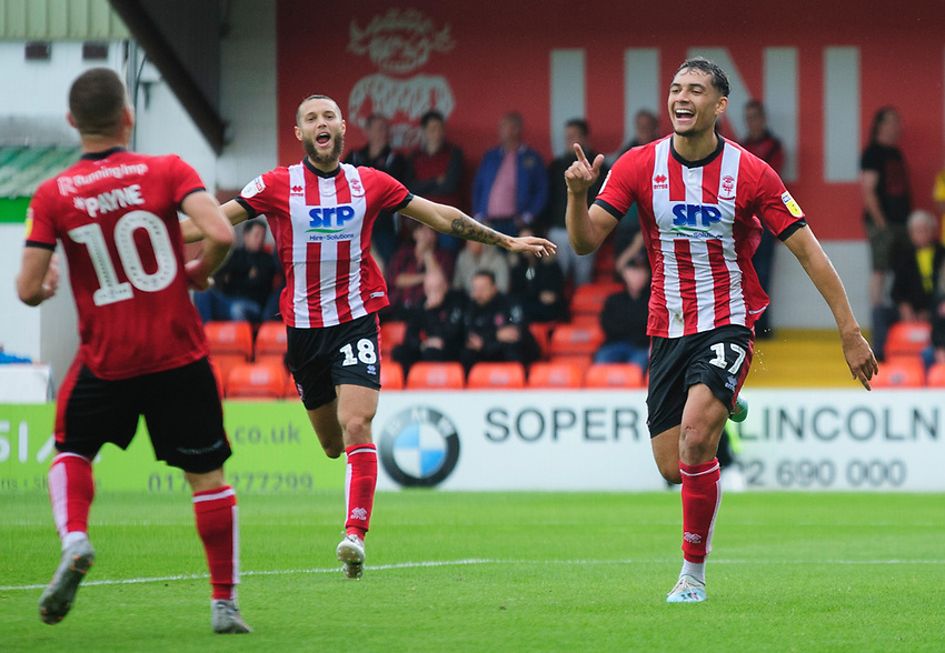 Lincoln City's Tyler Walker, right, celebrates scoring his side's second goal with team-mates, from left, Jack Payne and Jorge Grant<br /> <br /> Photographer Andrew Vaughan/CameraSport<br /> <br /> The EFL Sky Bet League One - Lincoln City v Fleetwood Town - Saturday 31st August 2019 - Sincil Bank - Lincoln<br /> <br /> World Copyright © 2019 CameraSport. All rights reserved. 43 Linden Ave. Countesthorpe. Leicester. England. LE8 5PG - Tel: +44 (0) 116 277 4147 - admin@camerasport.com - www.camerasport.com
