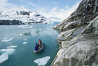 Tourists view glacier glacially carved rock bordering Nellie Juan lagoon and glacier, Prince William Sound, Alaska