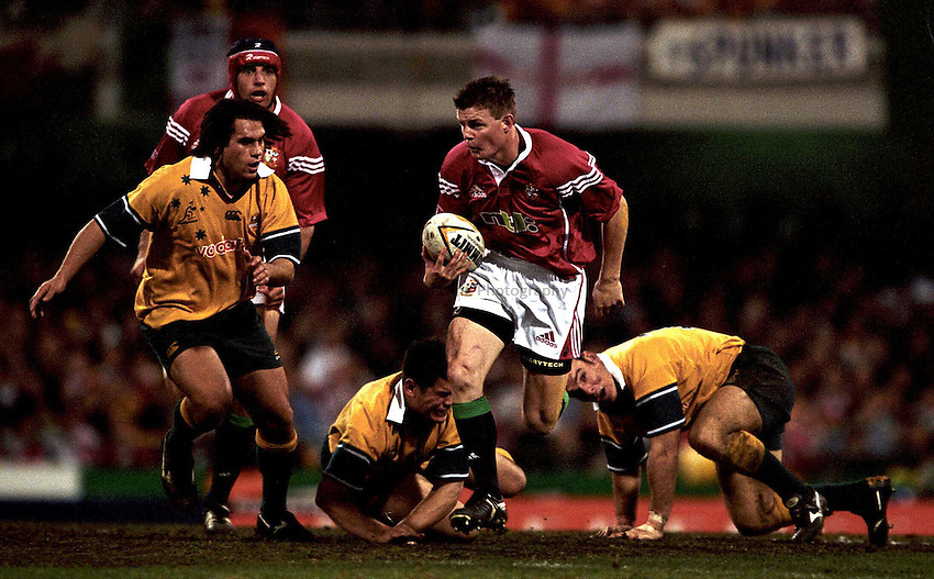 Photo. Richard Lane. .Lions Tour 2001. First Test, Australia v The Lions at the Gabba, Brisbane, Australia. 30/6/2001.Brian O'Driscoll leaves Daniel Herbert and Nathan Grey on the floor as George Smith looks to catch him.