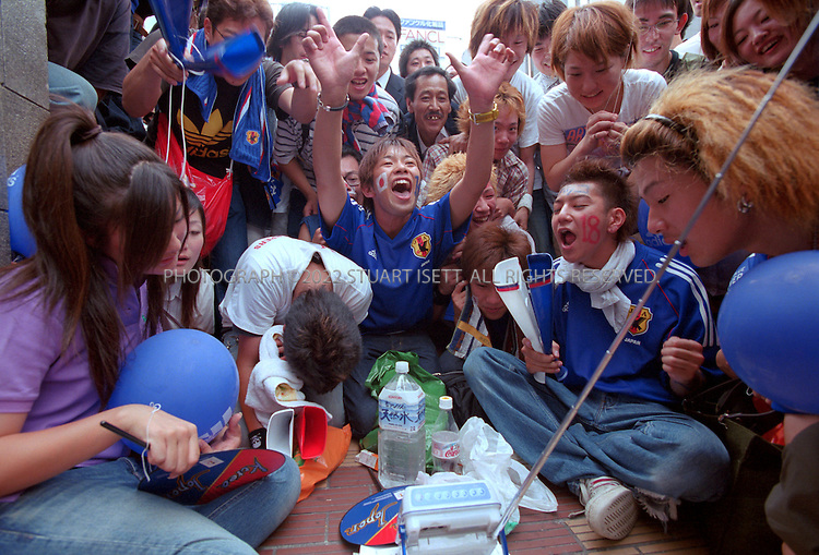 6/14/2002--Osaka, Japan..Japan supporters unable to get into the stadium for June 14th match against Tunisia watch the game on a minuture TV in downtown Osaka. After the match hundreds of young men, women and even office workers start jumping from Ebisubashi Bridge into the polluted Dotonbori River in Osaka after the Japanese soccer team beat Tunisia 2-0 and advanced into the second round of the World Cup.All photographs ©2003 Stuart Isett.All rights reserved.This image may not be reproduced without expressed written permission from Stuart Isett.