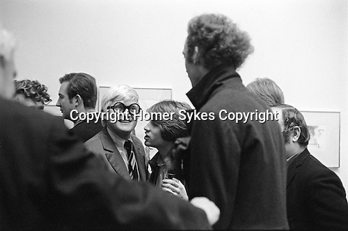 "Patrick Procktor and David Hockney. Hockney with his friend Peter Schlesinger whispering to him. RB Kitaj (extreme left just eyebrows showing, and Peter Blake right just half head behind PP.) Hockney opening night party at the  Kasmin Gallery 118 Bond Street London of ""Recent Etchings"". 1969"